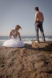 Pares hermosos jovenes que se sientan en rocas en la playa Imágenes de archivo libres de regalías