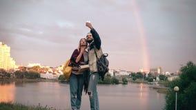 Pares hermosos jovenes que toman imágenes de un selfie, usando el smartphone para eso Puesta del sol y arco iris en fondo almacen de metraje de vídeo
