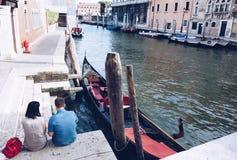 Pares hermosos jovenes que toman resto en la ciudad de Venecia que espera al gondolero un viaje en la góndola - Italia Imagen de archivo