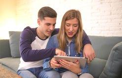 Pares hermosos jovenes 20s usando el ordenador digital del cojín de la tableta que sienta en casa compras de la sala de estar del Imagen de archivo libre de regalías