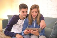 Pares hermosos jovenes 20s usando el ordenador digital del cojín de la tableta que sienta en casa compras de la sala de estar del Imágenes de archivo libres de regalías