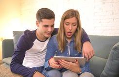 Pares hermosos jovenes 20s usando el ordenador digital del cojín de la tableta que sienta en casa compras de la sala de estar del Foto de archivo