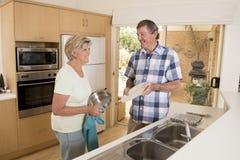 Pares hermosos mayores de la Edad Media alrededor 70 años en casa de la cocina feliz sonriente que lava los platos que parecen du Foto de archivo libre de regalías