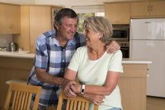 Pares hermosos mayores de la Edad Media alrededor 70 años junto en casa de la cocina feliz sonriente que parece dulce en el marid Foto de archivo libre de regalías