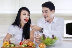 Pares hermosos que cocinan la ensalada en cocina imagen de archivo libre de regalías