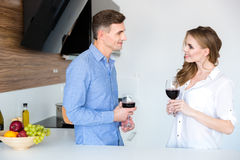 Pares hermosos que colocan y que beben el vino rojo en casa Imagenes de archivo