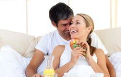 Pares hermosos que desayunan el mentir en la cama Foto de archivo libre de regalías