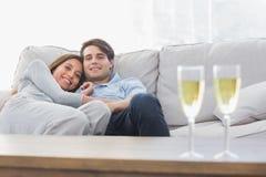 Pares hermosos que descansan sobre un sofá con las flautas del champán Imagen de archivo libre de regalías