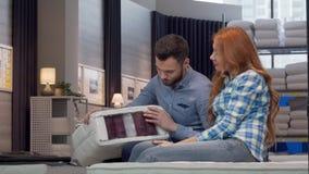 Pares hermosos que eligen el colchón ortopédico en la tienda de muebles junto almacen de video