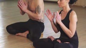 Pares hermosos que meditan junta haciendo la yoga almacen de video