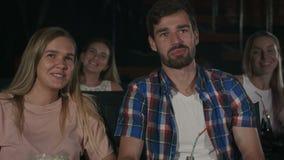 Pares hermosos que ríen y que susurran a su hombre durante una película en el teatro de película almacen de metraje de vídeo