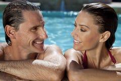 Pares hermosos que se relajan en piscina Foto de archivo
