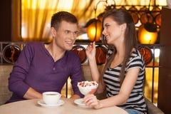 Pares hermosos que se sientan en café y la consumición Foto de archivo libre de regalías