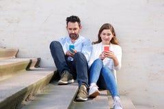 Pares hermosos que se sientan junto en escalera con los teléfonos móviles Imagen de archivo