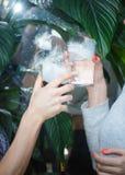 Pares hermosos que sostienen los cócteles del hielo seco en la fiesta Bebida púrpura con el vapor del hielo en el club, celebraci fotografía de archivo
