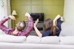 Pares hermosos que ven la TV el sentarse en el sofá en casa fotos de archivo libres de regalías