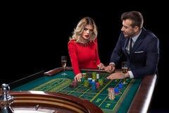 Pares hermosos y bien vestidos que juegan la ruleta en el casino Imagen de archivo libre de regalías