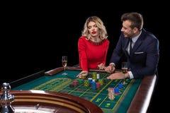 Pares hermosos y bien vestidos que juegan la ruleta en el casino Foto de archivo libre de regalías