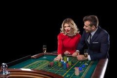 Pares hermosos y bien vestidos que juegan la ruleta en el casino Imagen de archivo