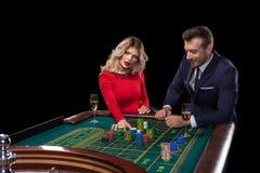 Pares hermosos y bien vestidos que juegan la ruleta en el casino Fotografía de archivo