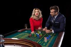 Pares hermosos y bien vestidos que juegan la ruleta en el casino Fotos de archivo