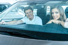 Pares heterosexuales jovenes que se sientan en un coche en la sala de exposición y que sonríen con Imagen de archivo