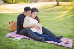 Pares hispánicos embarazadas en el parque al aire libre Imagenes de archivo