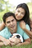Pares hispánicos en parque con el balón de fútbol Imagen de archivo libre de regalías