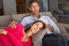 Pares hispánicos en Sofa Watching TV Foto de archivo libre de regalías