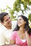 Pares hispánicos jovenes románticos que se relajan en parque Foto de archivo