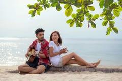 Pares hispánicos lindos que tocan la guitarra serenading en la playa en el amor y el abrazo, felices y relajar al aire libre en l imagenes de archivo