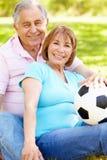 Pares hispánicos mayores que se relajan en parque con fútbol Imágenes de archivo libres de regalías