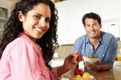 Pares hispánicos que comen el cereal y la fruta en cocina Imagenes de archivo
