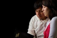 Pares hispánicos que estudian la biblia y que ruegan Fotos de archivo