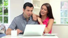 Pares hispánicos que miran el ordenador portátil mientras que come el desayuno almacen de metraje de vídeo