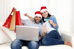 Pares hispánicos atractivos jovenes en compras en línea de la Navidad del amor con el ordenador Foto de archivo libre de regalías