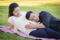 Pares hispánicos embarazadas en el parque al aire libre Imagen de archivo
