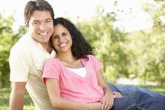 Pares hispánicos jovenes románticos que se relajan en parque Fotografía de archivo