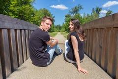 Pares holandeses atractivos jovenes que se sientan en el puente de madera Fotos de archivo libres de regalías