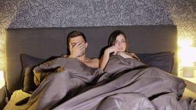 Pares, hombre y mujer jovenes, película asustadiza de observación en la cama en el dormitorio antes de la cama almacen de metraje de vídeo