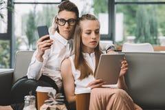 Pares homosexuales felices usando los dispositivos digitales en café Fotos de archivo