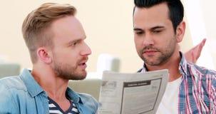 Pares homosexuales que hablan y que leen el periódico almacen de video