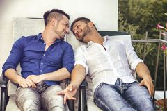 Pares homossexuais em cadeiras no balcão fotografia de stock royalty free