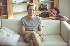 Pares homossexuais felizes que passam o tempo em casa fotografia de stock