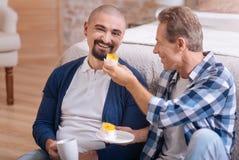 Pares homossexuais que comem queques em casa foto de stock
