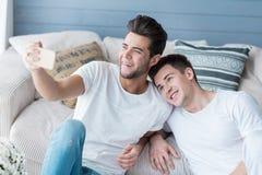 Pares homossexuais que tomam selfies em casa em um sofá fotografia de stock royalty free