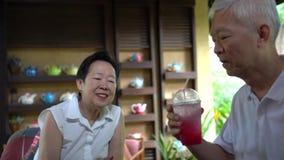 Pares idosos asiáticos que compartilham do amor e do cuidado simples das bebidas vídeos de arquivo