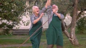 Pares idosos com mangueira de jardim filme