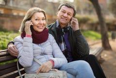Pares idosos com telefones celulares imagem de stock royalty free