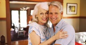 Pares idosos de sorriso que sentam-se em casa olhando a câmera foto de stock royalty free